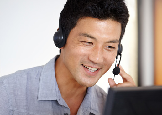 man with laptop and headset smiling