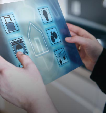 hands with a tablet on which different icons such as home, lock, music, bulb are shown