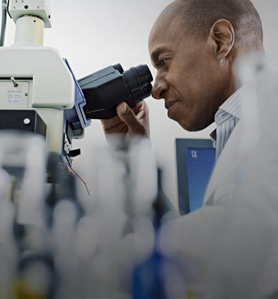 bald man looking through microscope