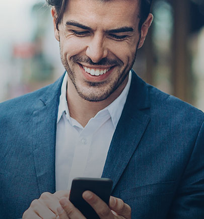 Man in blue suit smiling at smartphone