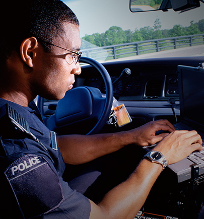 police officer typing in car