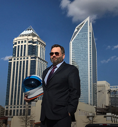 executive in dark glasses, tall buildings in background
