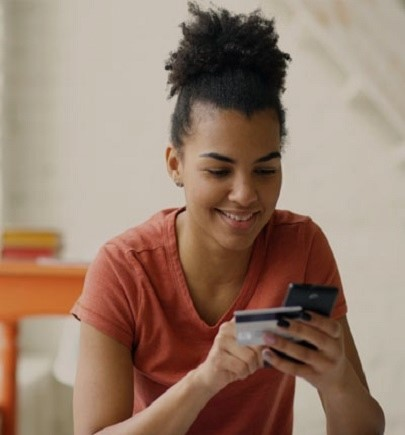 female smiling and looking at her debit card