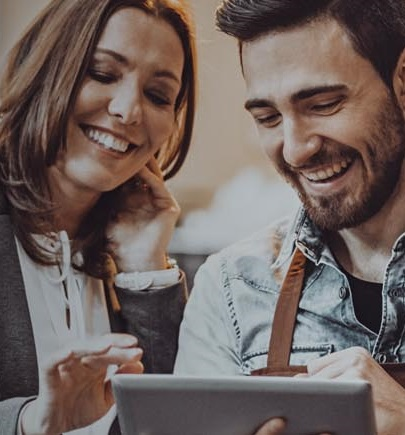man and woman smiling and looking at tablet