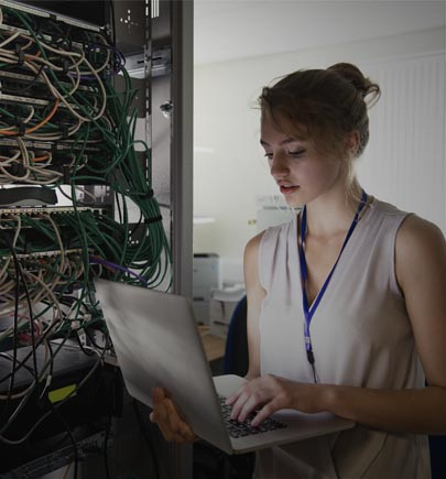 A young female technician is checking the server