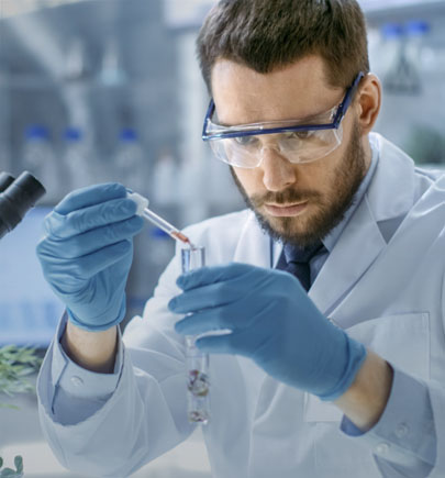 Man wearing safety goggles works in a lab