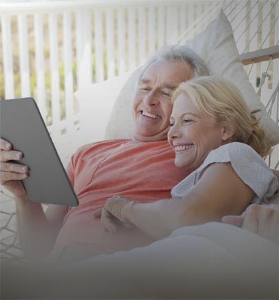 mature-couple-on-hammock-viewing-tablet