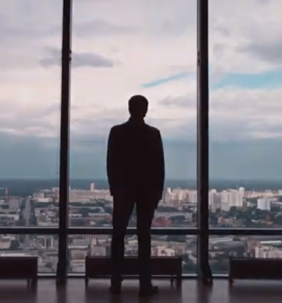 Man in tall building looking at sky and building through glass window/door