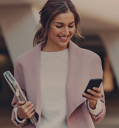 female executive smiling and looking at her mobile phone