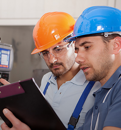 two manufacturing workers in helmet and looking at their notes
