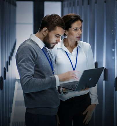 Businessman and woman on laptop in data center