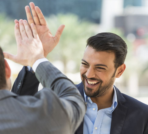 Two male coworkers give each other a high five