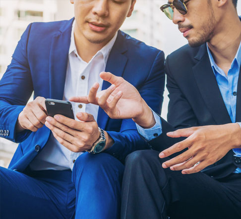 Two men in suits look at a smartphone