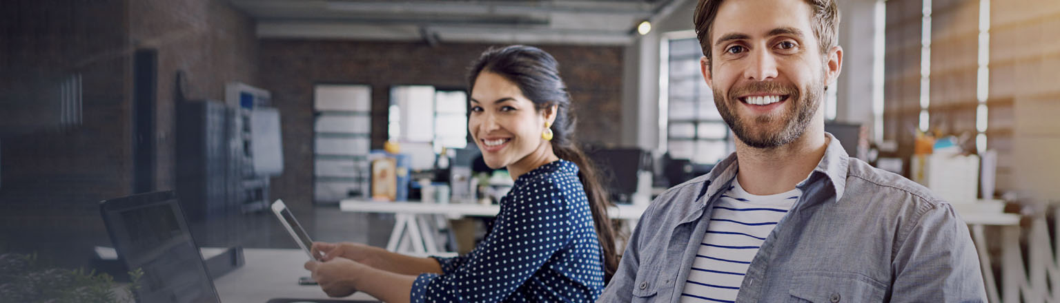 Man and woman in an office smile at the camera