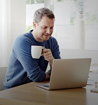 Man working on laptop with a coffee mug in his hand