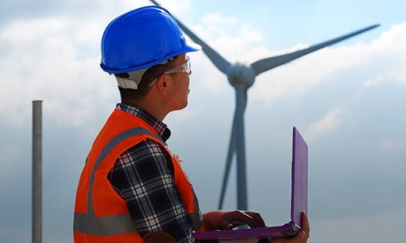 Man in hard hat with a laptop in a wind farm