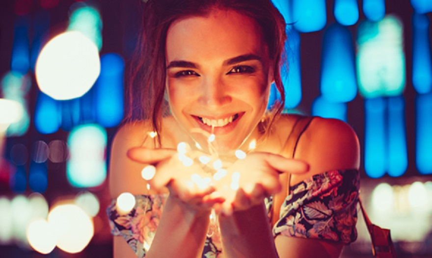lady smiling and holding light in her hands