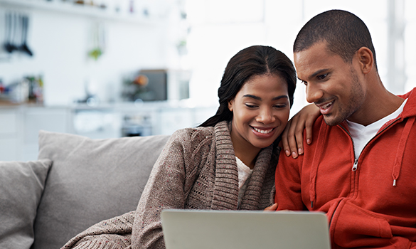 Couple at home looking at a laptop