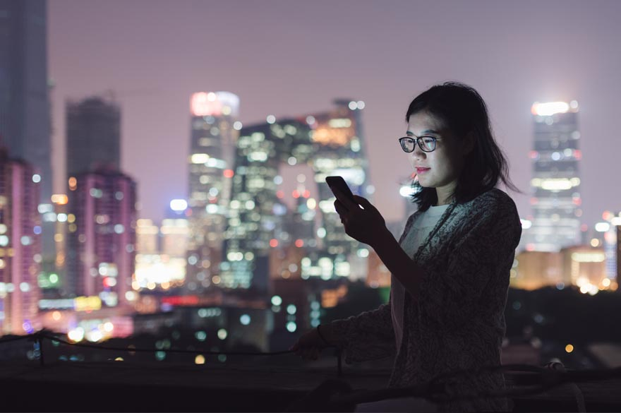 lady in the dark looking at her phone with a back drop of a city landscape