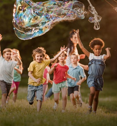children chasing a giant bubble outdoors
