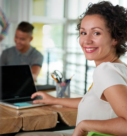 Smart woman working in office and smiling at camera