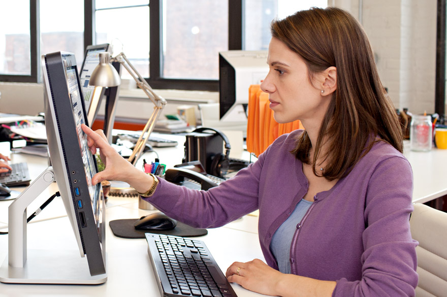 Woman working on touch screen monitor