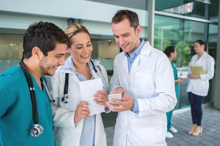 a bunch of doctors discussing something while holding a tablet with a smile