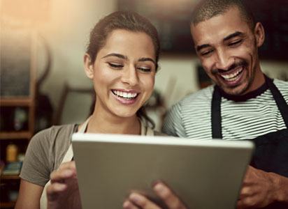 man and woman wearing aprons smile at a tablet