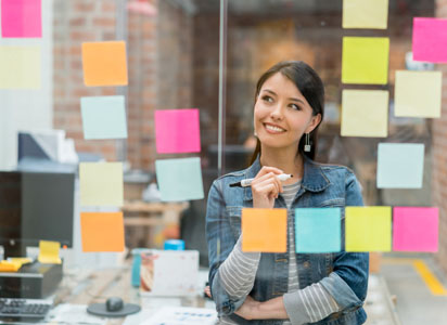woman in an office looks at sticky notes on a glass wall