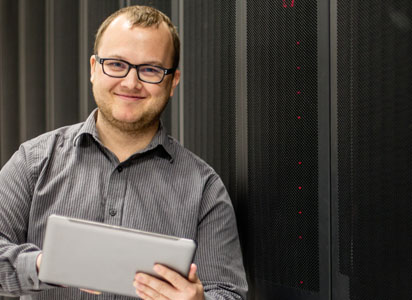 man in a data center holds a tablet