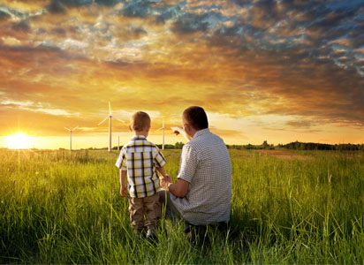 man shows young boy wind turbines in a field