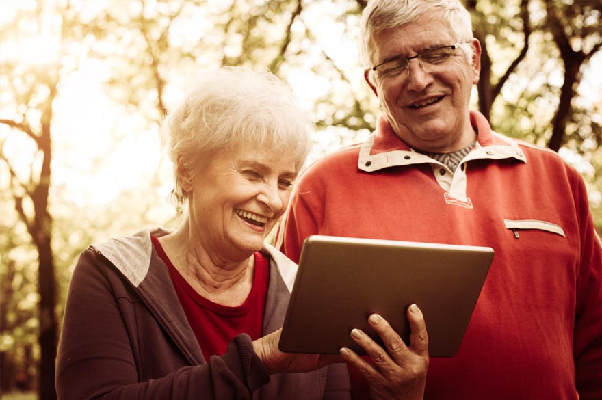 elderly couple watching tablet