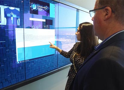 Woman with a businessman touching a large touchscreen panel