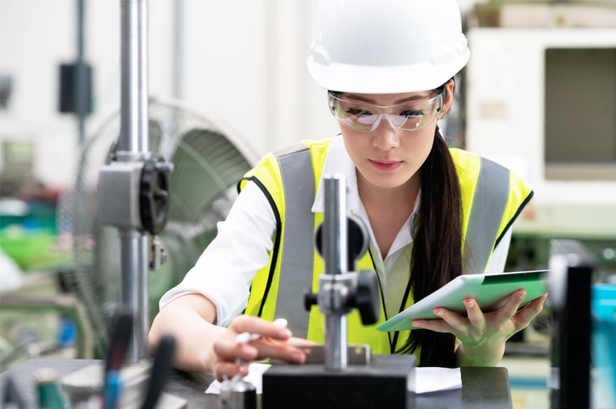 female worker with safety glasses and helmet working in construction site